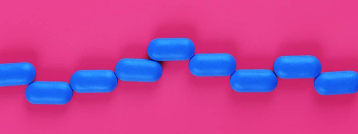 Blue pills on a pink background