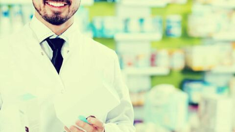 Chemist smiling holding medication