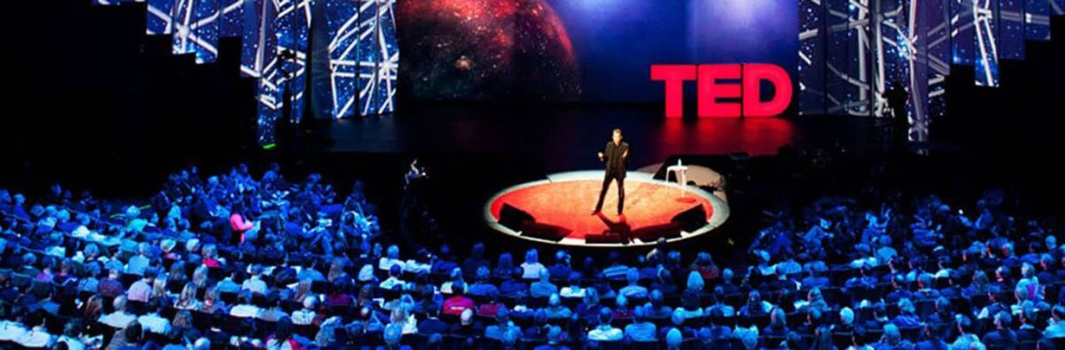 Man giving a TED talk on stage
