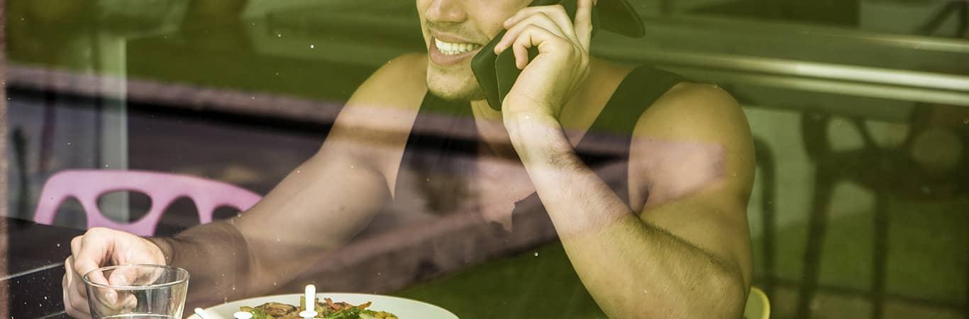 Man having breakfast talking on his mobile phone