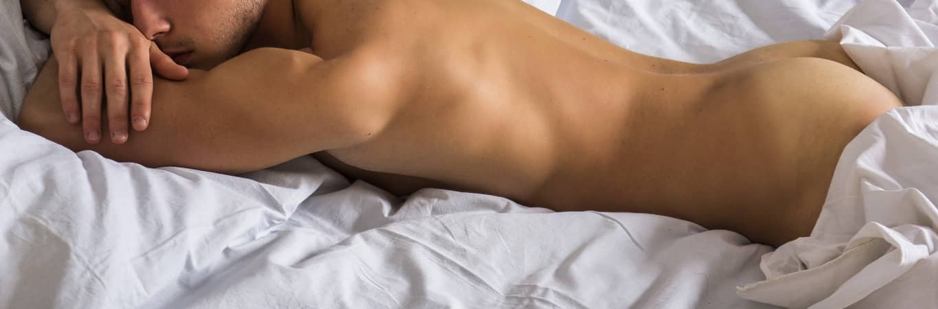 Man lying in bed naked