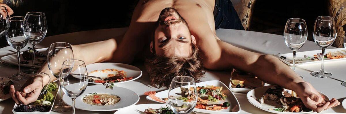 Man lying on table of food