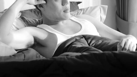Man lying with a pensive expression on bed