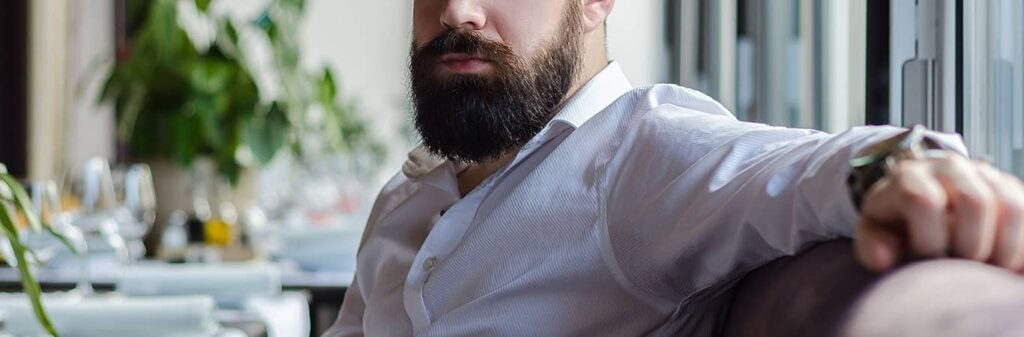 Man with beard in restaurant looking pensive