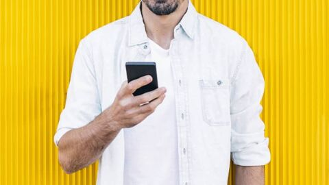 Man with beard standing by yellow wall with phone in his hands