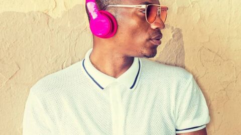 Man with sunglasses with pink headphones and white polo shirt
