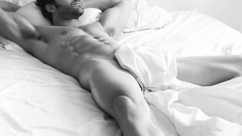Muscular man with abs and beard lying in bed naked
