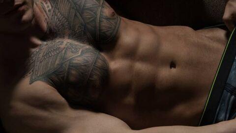 Muscular tatooed man lying down with underwear on