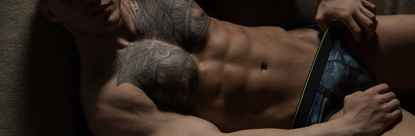 Muscular tatooed man lying down with underwear on