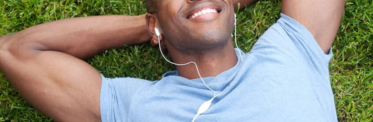 Smiling man lying on the grass with headphones