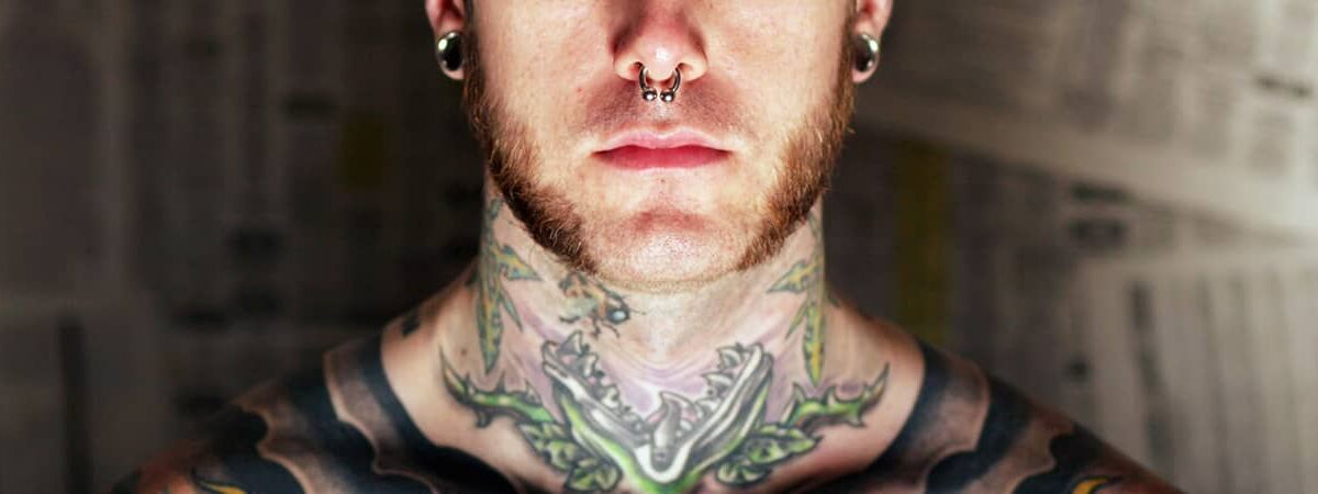 Tattooed man with nose ring and spacers and beard