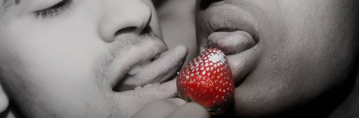 Two men licking a strawberry