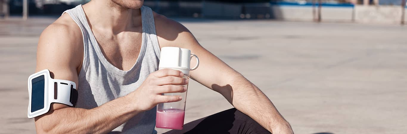 gay fit man with pink health drink