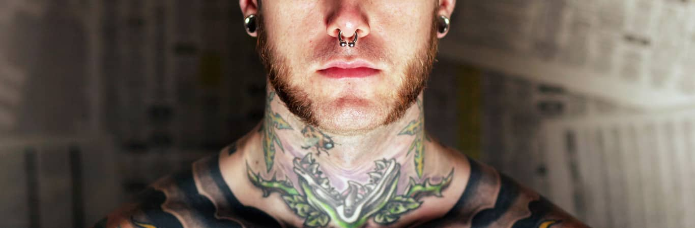 LGBTIQ tattooed man with nose ring and spacers and beard