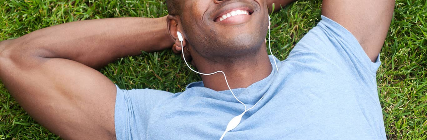 gay man lying on grass smiling with headphones