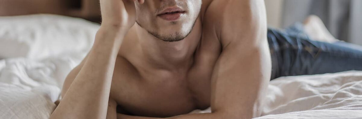 topless gay man lying on bed