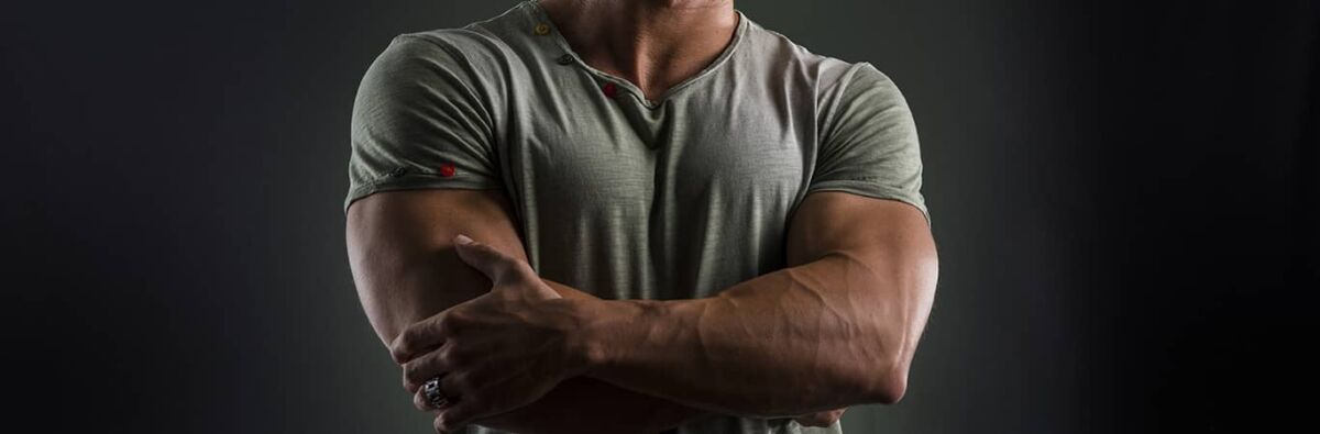 muscular gay man in grey shirt with crossed arms