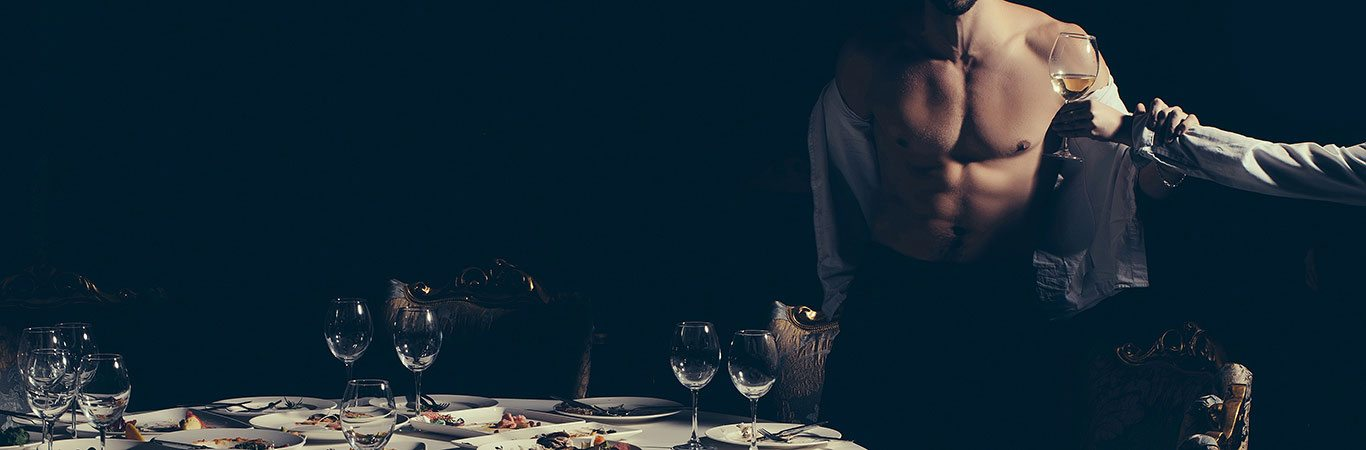Man-with-glass-of-wine-at-a-table-with-plates-of-food