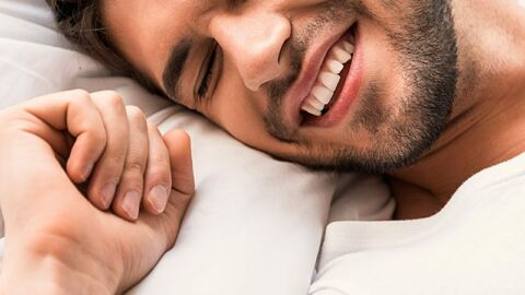 happy gay man with head on pillow