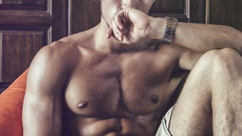 topless gay man sitting pensively