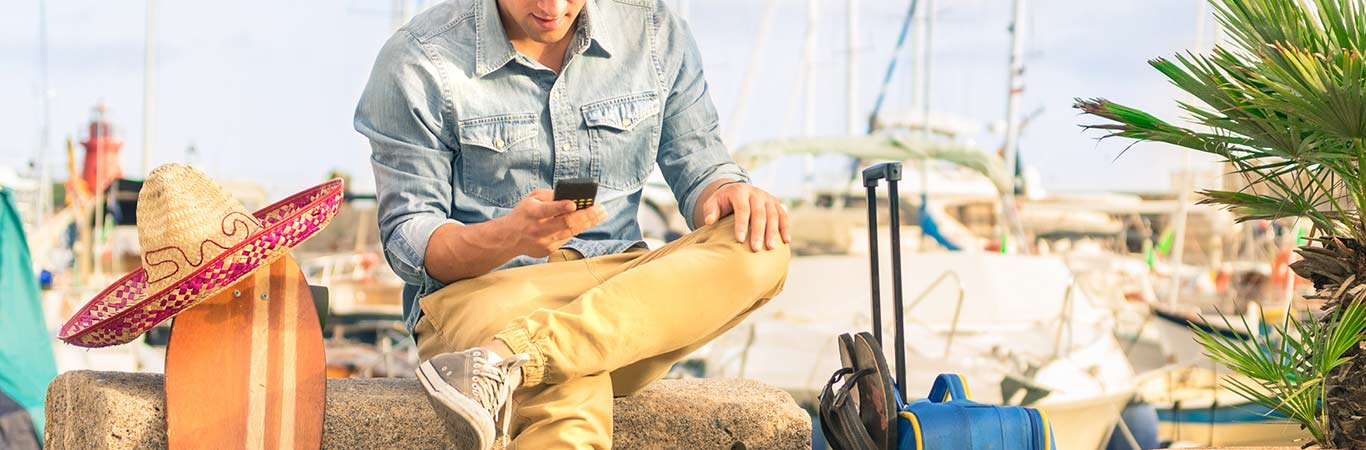 man on holiday sitting with suitcase