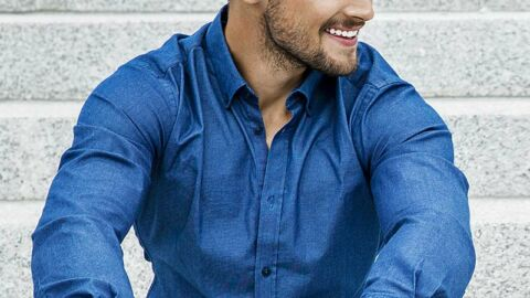 Seated man smiling wearing a blue buttoned shirt