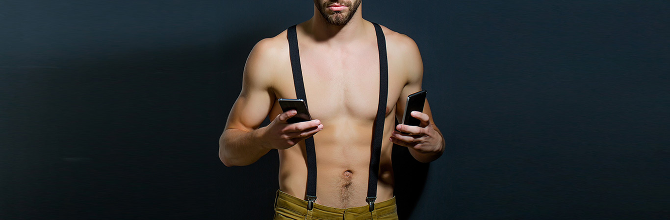 Shirtless man holding two phones