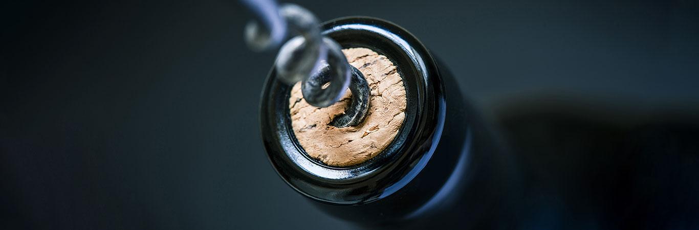 Corkscrew pulling cork from bottle of wine