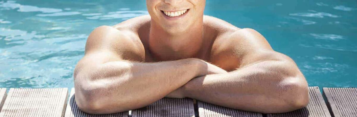 Very happy man smiling in a swimming pool
