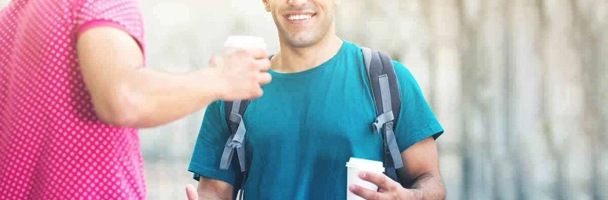 Smiling man having a takeaway coffee