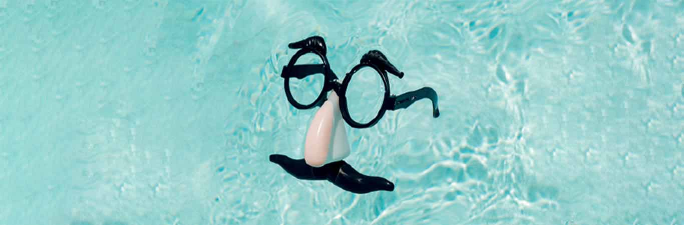 Comedy nose and glasses floating in swimming pool