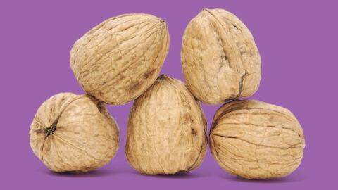 Five walnuts on purple background