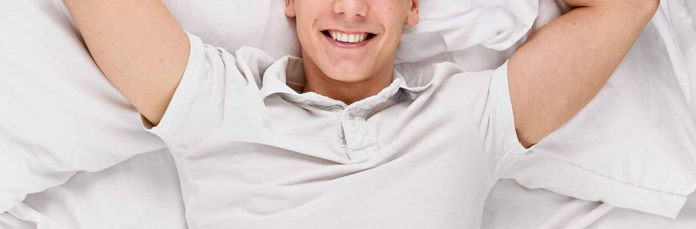 Happy man smiling in bed