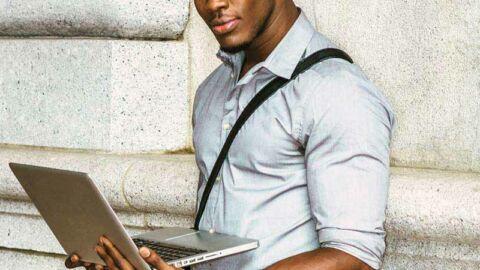 Smiling man holding laptop