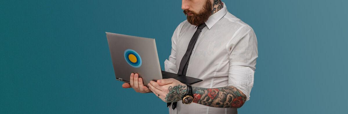 tattooed man holding laptop