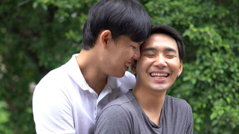 two asian guys in tender embrace in a park