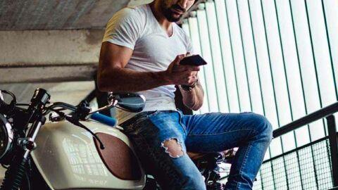 Man on motorbike looking at phone