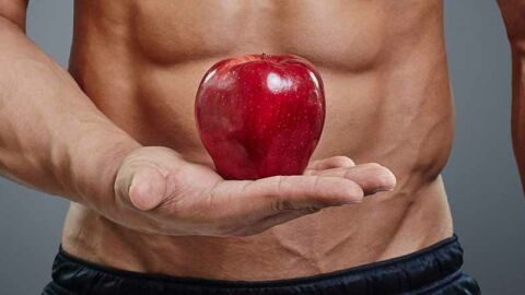 muscled man holding red apple