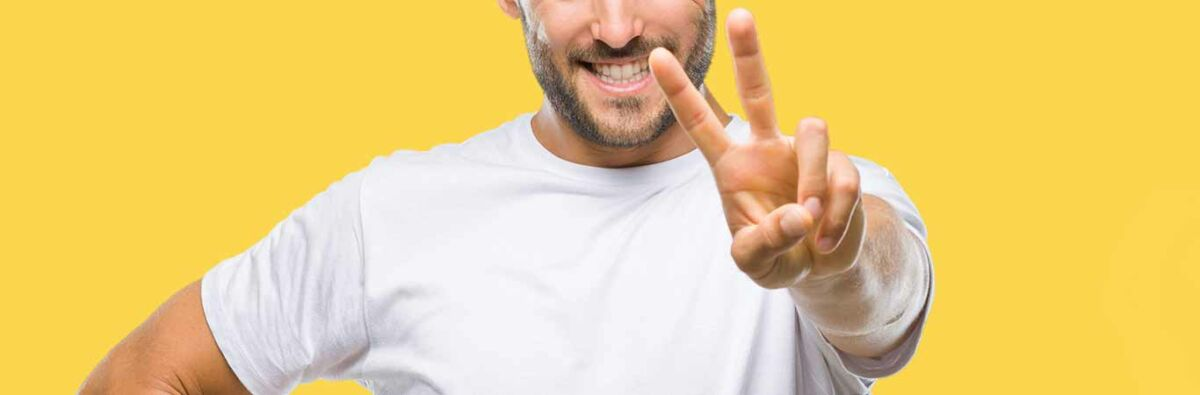 smiling man holding up two fingers