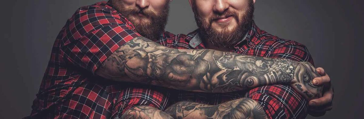 two tattood beary men hugging in checked shirts