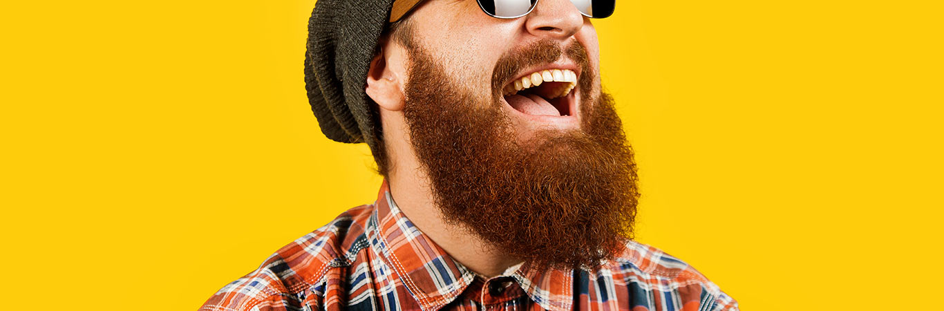 man in sunglasses laughing against yellow background