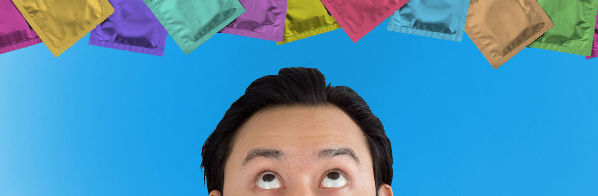 man looking up at coloured condoms