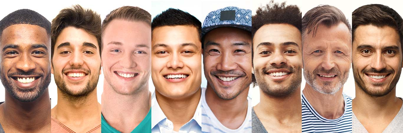 Eight smiling men of diverse backgrounds and ages