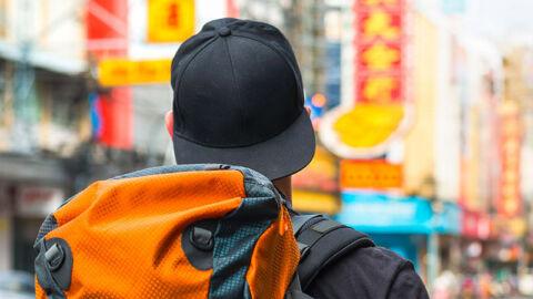 man wearing baseball cap and orange backpack in streets of bangkok