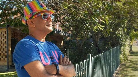 Johann man leaning against fence wearing UequalsU t shirt