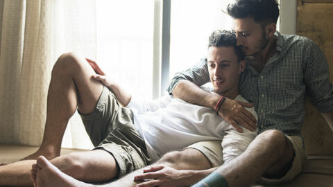two guys laying in bed affectionately