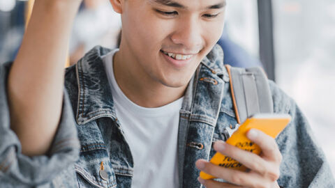 young man on bus smiles at yellow phone