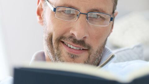 smiling man wearing glasses reading book