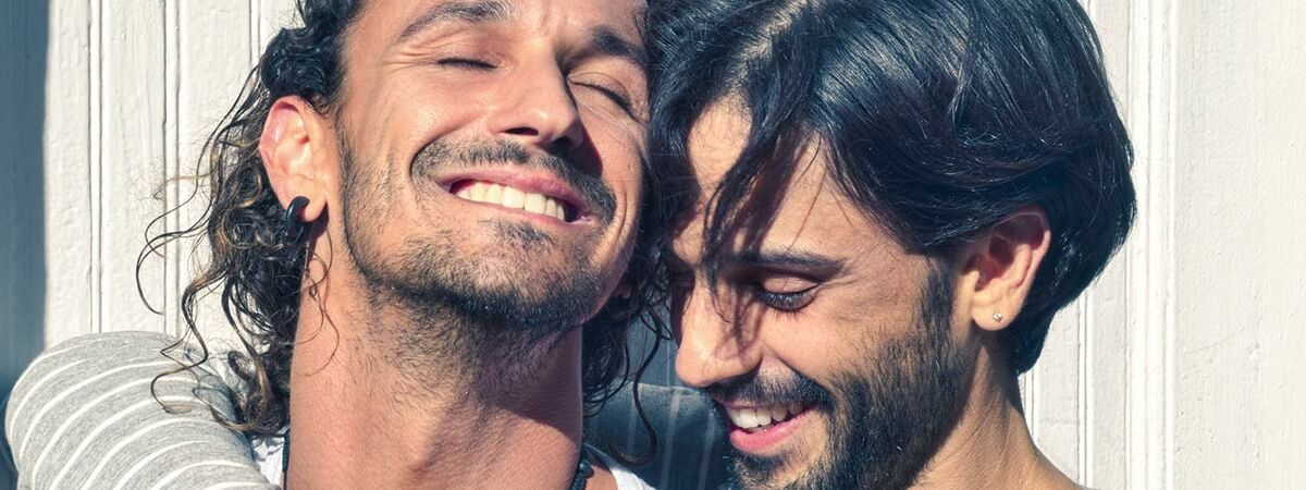 two dark haired men smiling and hugging