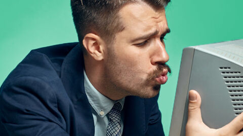 suited man kissing old computer monitor
